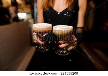 girl in a black dress and with red manicure holding in her hands two glasses with an alcoholic cocktail sour mix