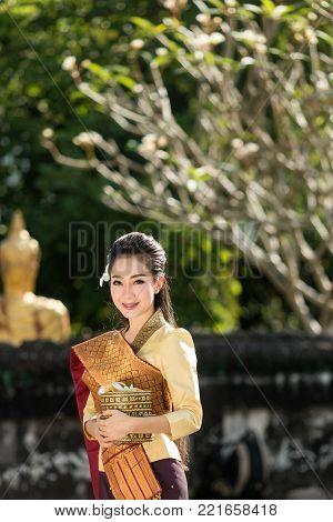 Beautiful Laos girl in Laos costume,Asian woman wearing traditional Laos culture standing at temple at countryside Laos.