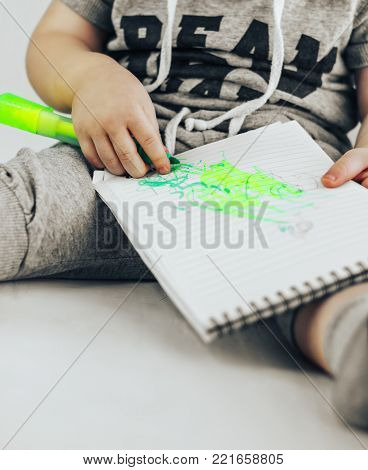 A boy draws. Child's drawing. The child sitting near window and draws in a notebook with white paper.