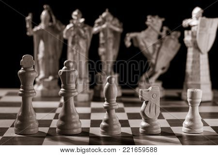Classic white chess pieces such as king, queen, bishop, knight, rook and the same pieces in the form of medieval figures on the background. Selective focus on classic pieces