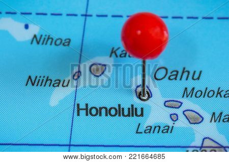 Close-up of a red pushpin on a map of Honolulu, USA.