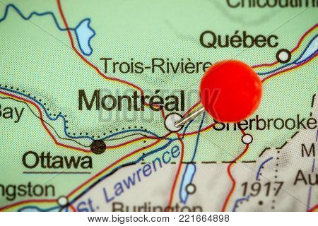 Close-up of a red pushpin on a map of Montreal, Canada.