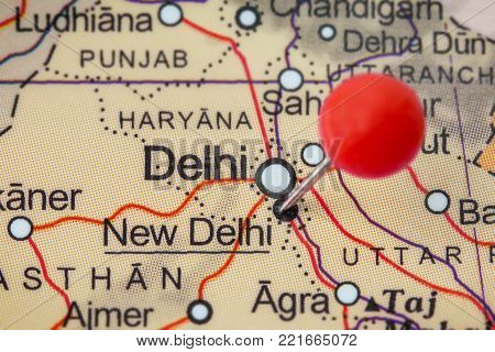 Close-up of a red pushpin in a map of New Delhi, India.