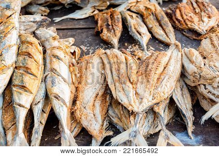 Close-up image of different types of dried fish on wooden table, beer snack concept