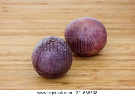 Close-up of two whole passion fruits (passionfruit, purple granadilla (Passiflora edulis)) on a wooden table.
