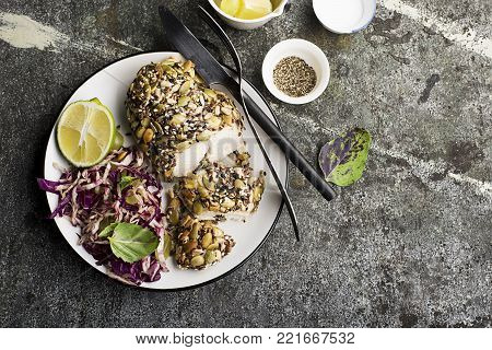 A healthy snack lunch. Baked chicken breast in breaded LSA pumpkin seeds, flax seeds, sunflower seeds, almonds for crispy appetizing crust with radicchio salad, green grapes with basil in a plate on.