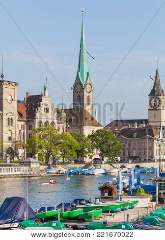 Zurich, Switzerland - 1 August, 2014: the Limmat river and well known architectural landmarks of the city along it: Zurich City Hall, Fraumunster, clock tower of the St. Peter Church. Zurich is the largest city in Switzerland.