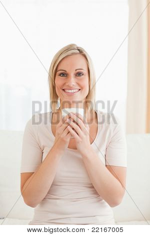 Portrait of a smiling woman holding a cup of tea while looking at the camera