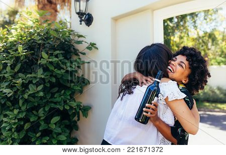 African woman greeting and embracing female friend for having a new house. Smiling young woman with wine bottle congratulating her friend. Housewarming with friends.
