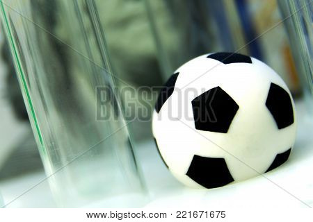 Souvenir soccer ball with medical test tubes against the background of one hundred dollar bill. Macro. Concept money and sports, medicine and football, corruption and doping.