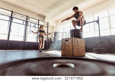 Couple During Intense Workout Session At Health Club