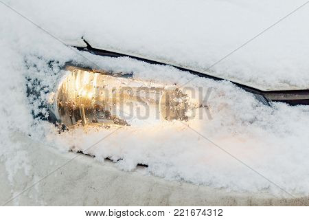 Snow covered and illuminated car headlight. Safety on winter roads