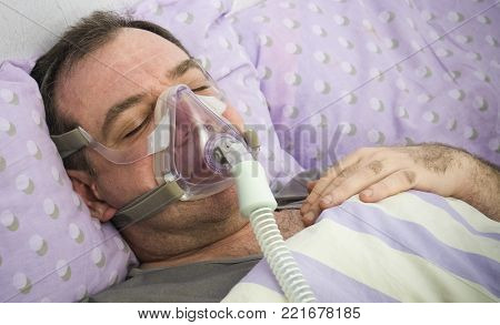 Man Lying On Bed With Sleeping Apnea And CPAP Machine