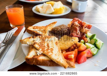 Close up plate with toasts, meat, fresh cucumbers and tomatoes and glass of juice on table. Delicious meal concept