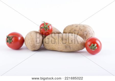 Potatoes and tomatoes on a white background. Potatoes on a white background. Red tomatoes with potatoes