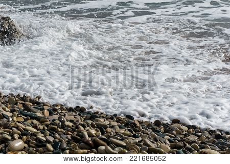 Photo of frothy sea, pebble by day