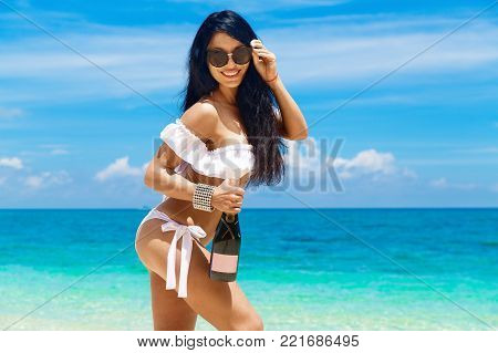 Beautiful Brunette Girl With Long Hair In Bikini With Bottle Of Champagne On A Tropical Beach. Summe
