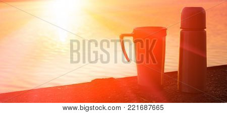 Active lifestyle concept Travel. Thermo Thermos and mug on the edge of the pier. majestic sunrise. soft selective focus. blurred.