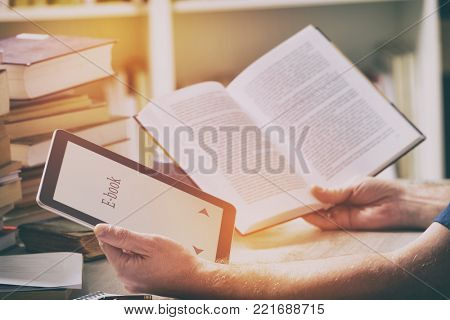 Man sitting in a library and holding in hands a modern ebook reader and paper books, bookshelf in the background