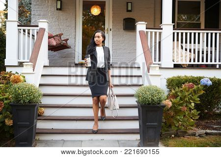Businesswoman With Cup Of Coffee Leaving Suburban House For Work poster
