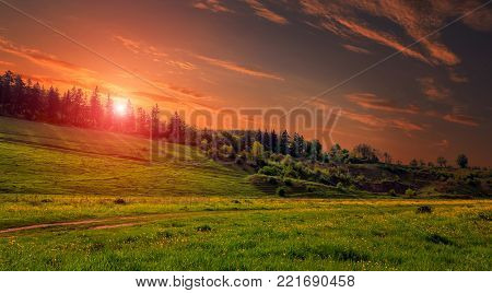 Rural landscape with a hill. Green meadow under sunset, colorful sky with clouds Dramatic morning scene. Beautiful natural landscape