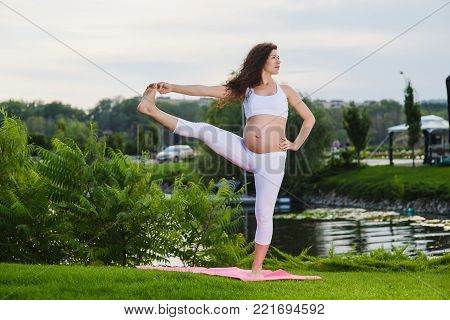 Beautiful young pregnant woman. Pose capture big toe on nature outdoors. Utthita Hasta Padangushthasana. Lake, river in the background.