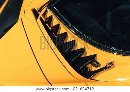Luxury yellow vintage roadster fragment, aerodynamics air intake grille on a car bonnet