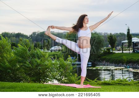 Beautiful young pregnant woman doing yoga outdoors. Pose capture big toe on nature outdoors. Utthita Hasta Padangushthasana. Lake, river in background.
