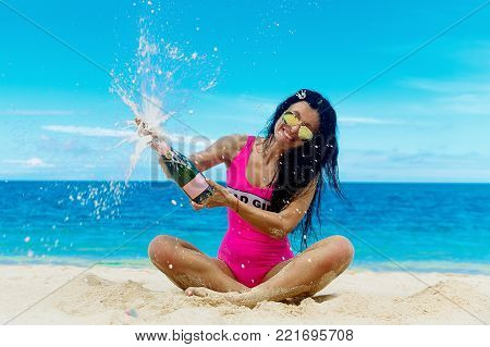 Beautiful brunette opens a bottle of champagne with splashes on the tropical beach. The sea in the background. Summer vacation concept.