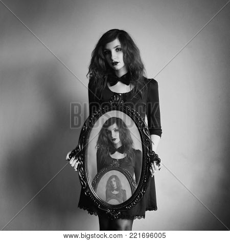 Woman with long curly hair in dress with bow tie. Black and white art monochrome photography. Black and white creative photography. Black and white conceptual image. Beautiful black and white background. Black and white portrait