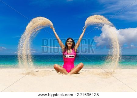 Beautiful brunette having fun in sand on the shore of a tropical beach. Summer vacation concept.