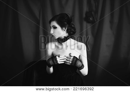 Black and white art monochrome photography. Black and white creative photography. Black and white conceptual image. Beautiful black and white background. Black and white portrait. A woman with curly hair in a black dress and retro makeup.