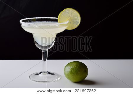Margarita cocktail and lime on black and white background.