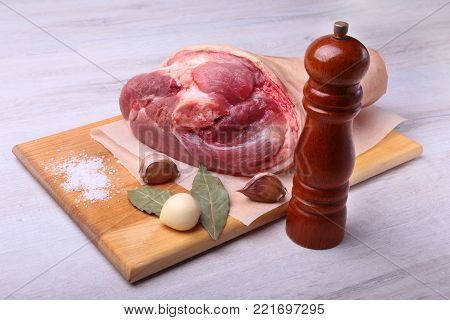 Raw pork knuckle, Aromatic dried bay leaves, garlic, sea salt, pepper grinder and spices on a cutting board. Selective focus. Ready for cooking