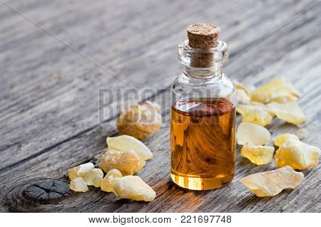 A bottle of frankincense essential oil with frankincense resin on a wooden table with copy space
