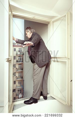 Desperate bankrupted businessman thinking to jump down from window to street