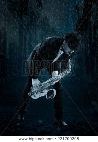 Saxophonist. Man playing on saxophone under rain