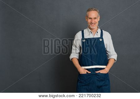 Mature small business owner standing and looking at camera isolated on grey wall. Happy man in work clothes with apron standing. Portrait of successful owner smiling with copy space.
