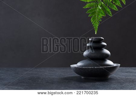 Elegant and luxury spa concept with massage stones and fern leaf. Hot stones on slate plan with black background and copy space. A drop of water slips from a wet fern leaf over a stack of black stones