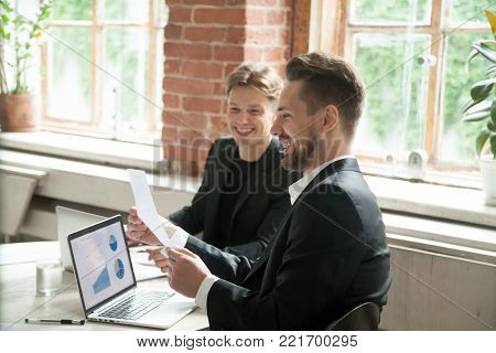 Two satisfied executives discussing company growth project success financial statistics with rising graphs on laptop screen, businessman holding document showing increasing stats to partner in office