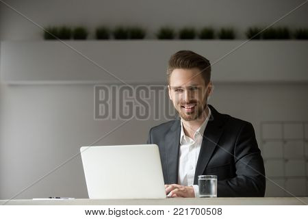 Smiling young businessman in suit working on laptop looking at camera, successful attractive professional executive sitting at office desk using computer, friendly company ceo at workplace, portrait