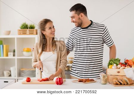 people and healthy eating concept - happy couple cooking food at home kitchen