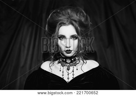 Black and white art monochrome photography. Black and white creative photography. Black and white conceptual image. Beautiful black and white background. Black and white portrait. A woman is a vampire with pale skin and hair in a black dress