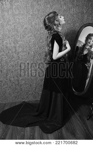 Black and white art monochrome photography. Black and white creative photography. Black and white conceptual image. Beautiful black and white background. Black and white portrait. Woman with long curly hair in a black and red dress and choker on her neck.