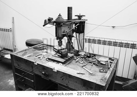 Workplace with a drill and vice. Work at a factory. Drilling Machine. Black and white art monochrome photography. Black and white creative photography. Black and white conceptual image. Beautiful black and white background.