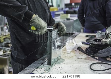 Close up of worker with tools equipment on factory manufacturing of modern metalworking production of industrial steel ventilation air systems, toned