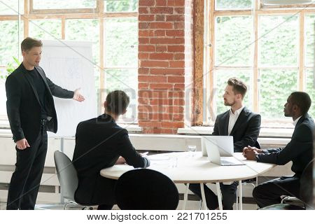 Company ceo giving presentation to diverse group working with flipchart at meeting in modern loft office, successful coach teaching businessmen on corporate training, team leader presenting project