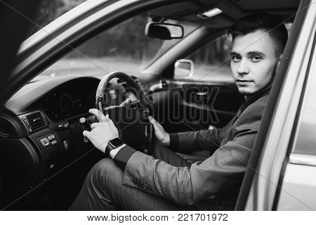 Black and white art monochrome photography. Black and white creative photography. Black and white conceptual image. Beautiful black and white background. Black and white portrait. Successful businessman in a dark business suit with tie in the car. Stylish