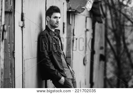Young attractive cheerful man with dark hair with a beard. Black and white art monochrome photography. Black and white creative photography. Black and white conceptual image. Beautiful black and white background. Black and white portrait.