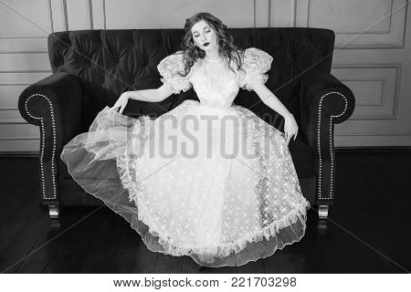 Woman with long curly hair in a white vintage wedding dress. Black and white art monochrome photography. Black and white creative photography. Black and white conceptual image. Beautiful black and white background. Black and white portrait.